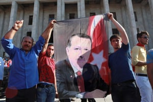 People hold a banner depicting Erdoğan as they gather outside the Turkish parliament.