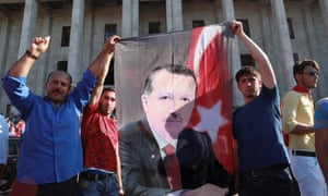 People hold a banner depicting Recep Tayyip Erdoğan as they gather outside the Turkish parliament in Ankara on 16 July.