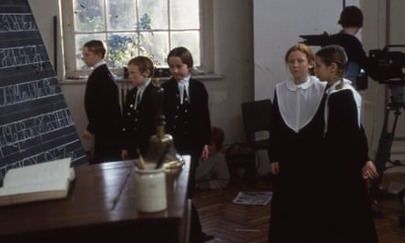 Pupils in old-fashioned uniforms in classroom, camera in background
