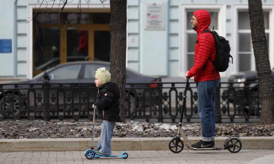 A father and child on their scooters