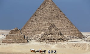 Tourists ride in horse carts near the Giza pyramids, a site where many tourists are targeted by souvenir sellers.