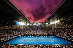 Rafael Nadal serves to Alex de Minaur as the sun sets.