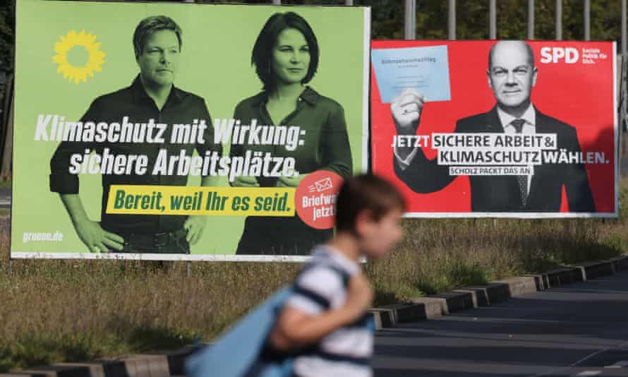 A boy walks past election campaign billboards for the German Greens and the Social Democrats.