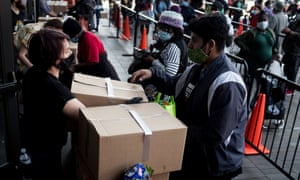 Volunteers help people distributing care packages with food donations from the Food Bank for New York City in Brooklyn.