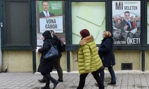 People walk past campaign posters of Jobbik's leader, Gábor Vona, and Viktor Orbán in Gyöngyös, Hungary.