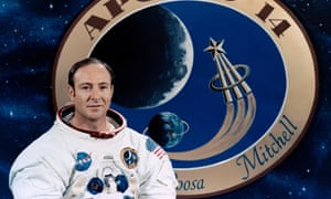 Edgar Mitchell, posing in front of a graphic of the Apollo 14 mission patch.