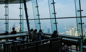 People sit in a Hong Kong cafe with view of harbour