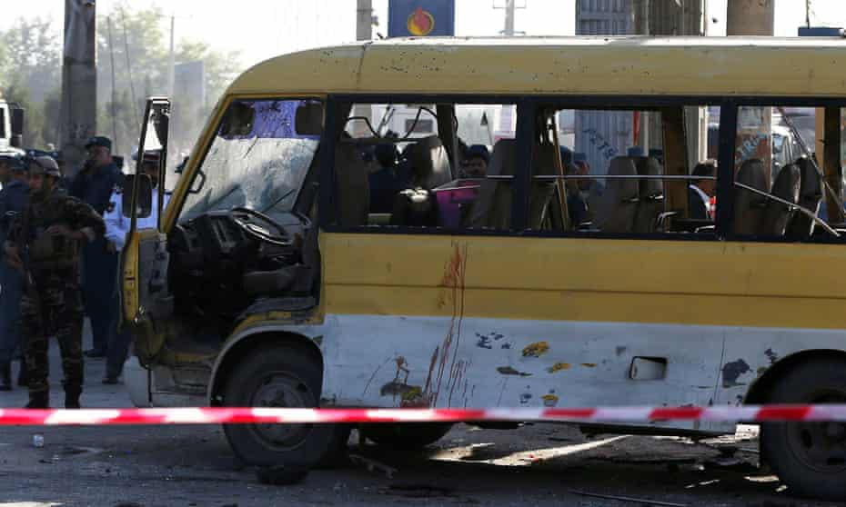Afghan security forces inspect the damage of a minibus that was hit by a suicide attacker in Kabul.