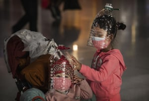 Beijing, China Children wear plastic bottles as makeshift masks while waiting to check in for a flight at Beijing Capital airport