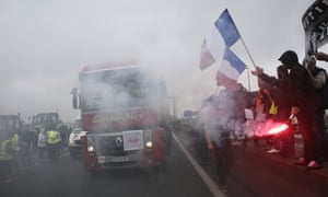 People cheer and wave flares and French flags as a protesting trucker blocks the highway near Calais