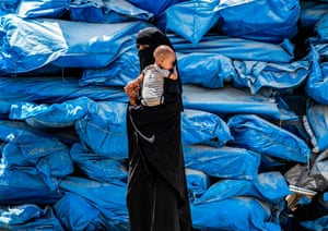 Al-Hol, SyriaA woman wearing a niqab (full face veil) walks carrying an infant at a camp for displaced people in al-Hasakeh governorate as people collect UN aid packages