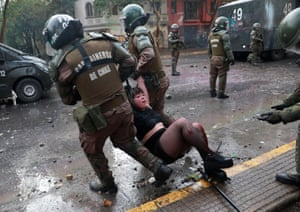 Santiago, Chile Riot police officers detain an injured demonstrator during an anti-government protest