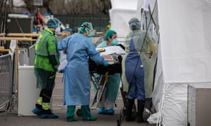 Health workers attend a patient at an emergency field hospital in March in Lombardy, Italy