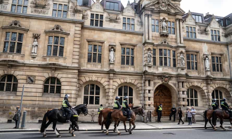 Police patrolling outside Oriel College earlier in the day. The Rhodes statue is on the second floor wall above the main door.
