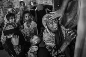 A cleric touches the head of a Rohingya refugee woman as she asks for food as they rest in a madrasa