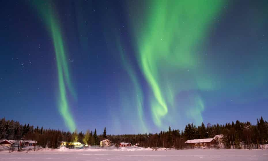 The northern lights in the sky over a frozen lake at Levi, Finland.