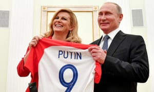 Croatian president Kolinda Grabar-Kitarovic (L) offers to Russian president Vladimir Putin a jersey of the Croatian national football team bearing the name Putin.