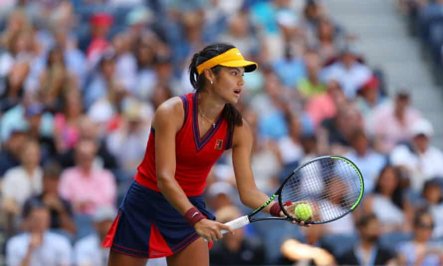 Emma Raducanu in a red and blue outfit with a yellow visor standing ready to serve, viewed from side on