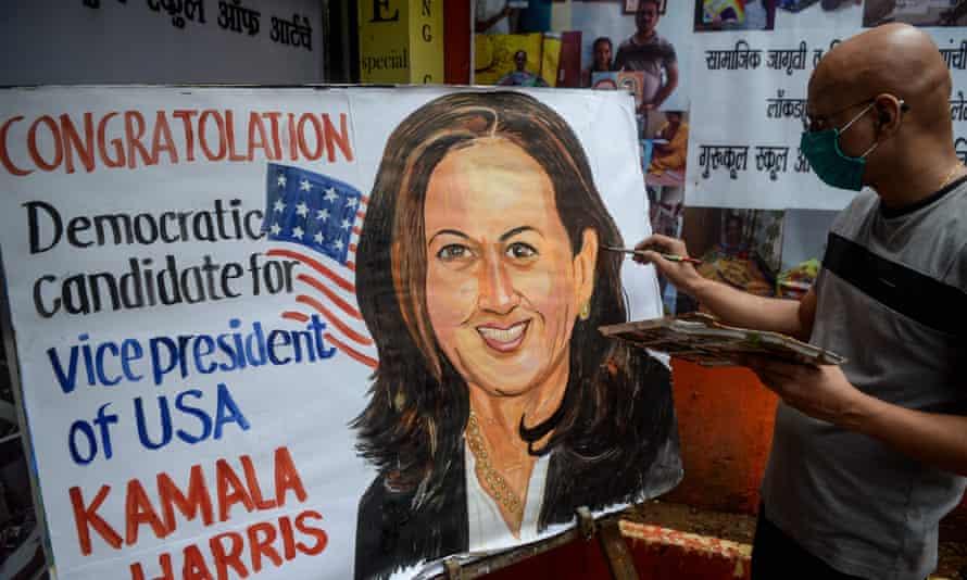 A man paints a poster depicting Kamala Harris in Mumbai