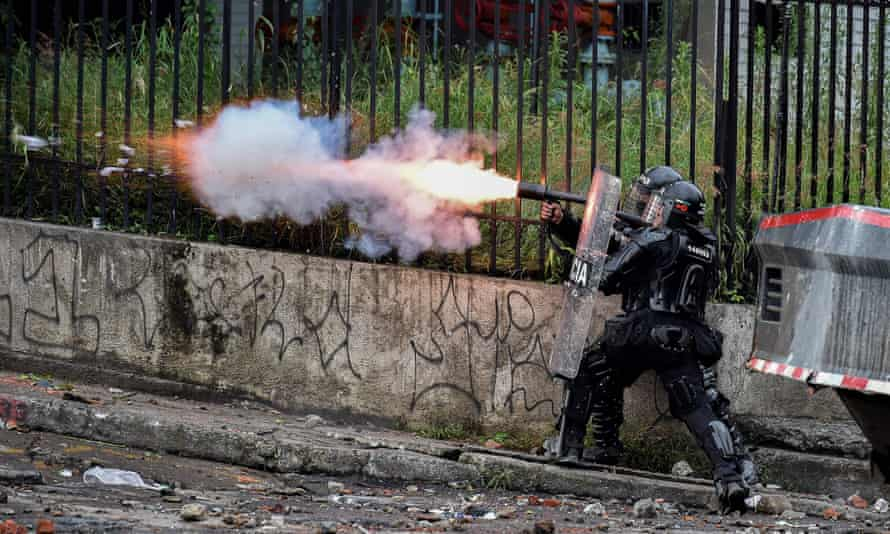 Riot police officers fire teargas at demonstrators in Cali on 10 May.