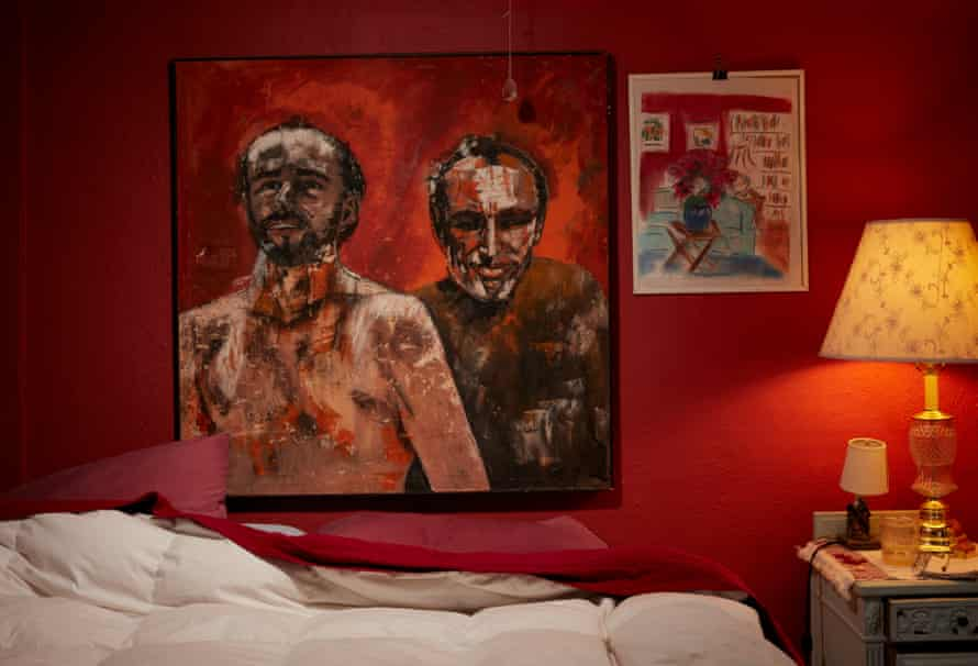 Painting of two men on a red background, above a bed