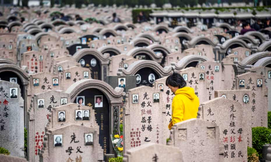 A woman decorates a grave at a cemetery in Shanghai