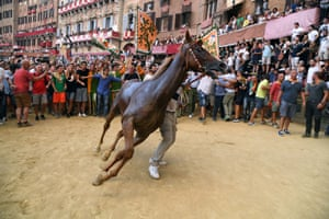 A member of the Selva parish handles his horse Remorex after winning the historical Palio horse race in Siena, Italy.