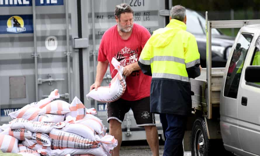 A man loads up sandbags to his car at Pimpama on the Gold Coast.