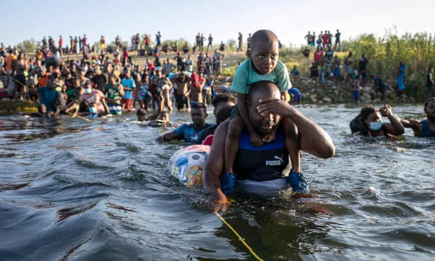 child rides on man's shoulders as man wades through water and covers his eyes