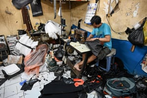 Jakarta, Indonesia. A man at his sewing machine in a bag workshop