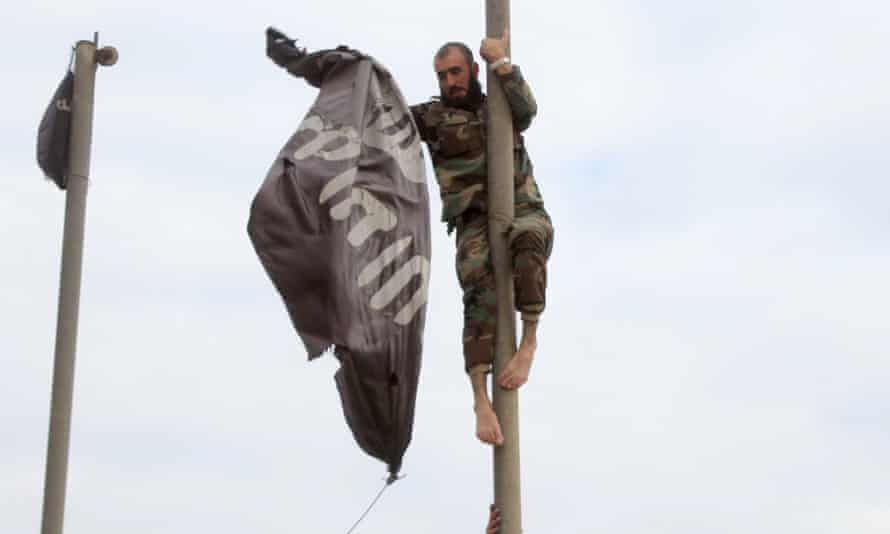 A Syrian government soldier removes an Isis flag from an Aleppo power plant after the facility was recaptured.