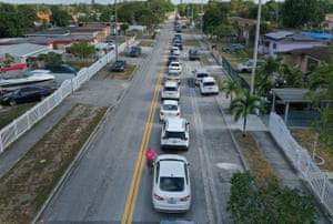 An aerial view shows vehicles lining up to receive unemployment applications being given out at the John F Kennedy Library on 8 April in Hialeah, Florida. The city is distributing the printed unemployment forms to residents as people continue to have issues with access to the state's unemployment website.