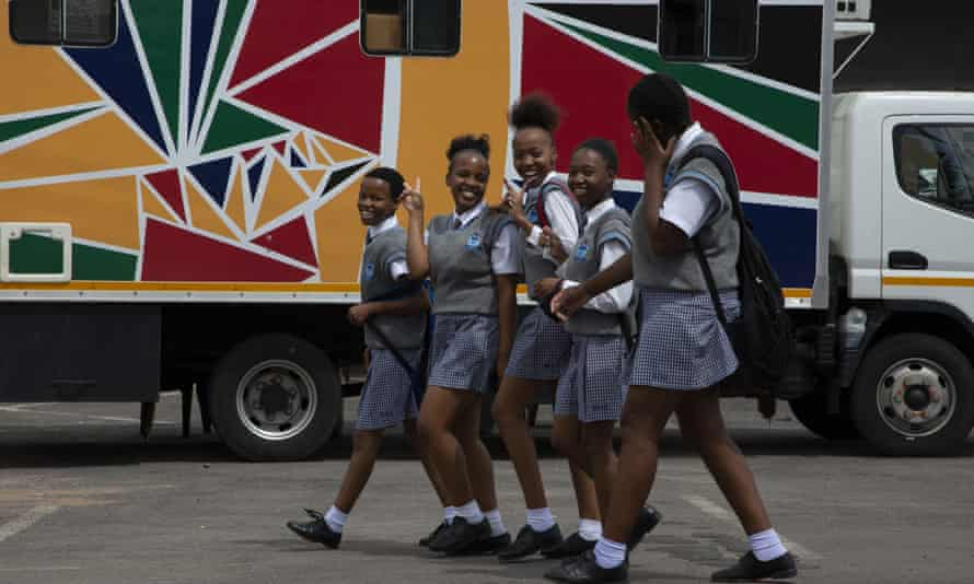 Schoolgirls pass the Mobile Reproductive Health Clinic in the town of Sushangio, near Pretoria, South Africa. Experts say such outreach projects will suffer greatly from aid cuts.