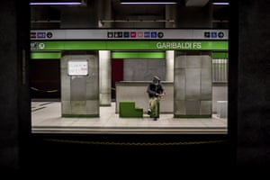 A man wears a mask as he waits in a subway station, in Milan