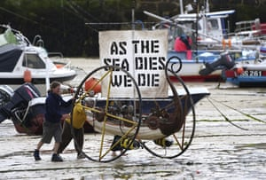 Climate activists push a boat on wheels with a message in the harbour at St. Ives