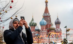 a man snaps a picture near the Kremlin on a smartphone