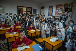 Journalists and officials crowd in a classroom as Tibetan Buddhist novice monks take part in a class for 'Living Buddhas'