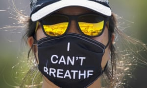 A woman wearing a face mask reading, 'I can't breathe'