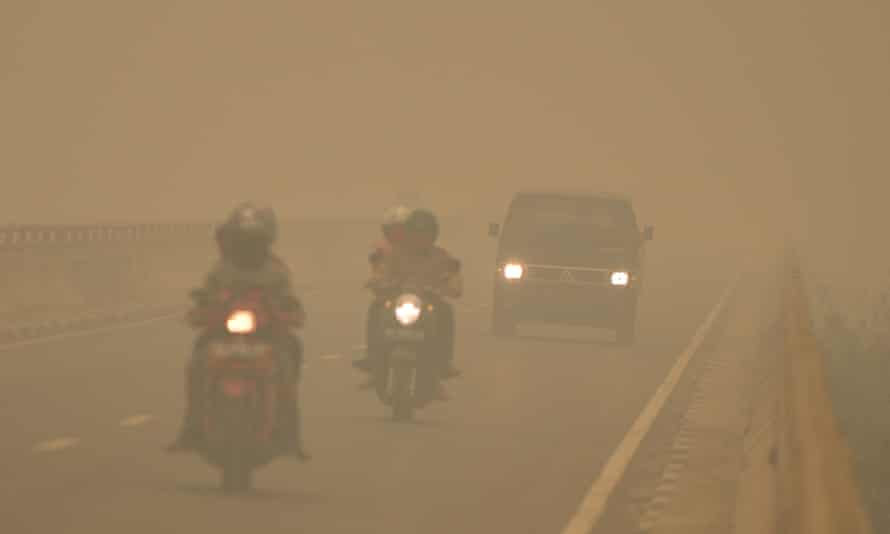 Commuters drive through thick haze in Tumbang Nusa, Central Kalimantan, on October 25, 2015. Indonesia has put warships on standby to evacuate people affected by acrid haze.