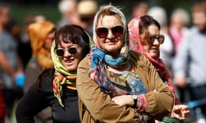 Women wearing headscarves as tribute to the victims of the mosque attacks are seen before Friday prayers at Hagley Park outside Al-Noor mosque in Christchurch.