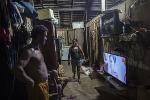 Villagers watch a soap opera in their home in the village Tekohaw, in Para state, Brazil. Daily life in the remote Tembe indigenous villages in the Amazon jungle of Brazil mixes tradition and modernity
