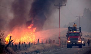 A makeshift fire truck puts water on a wildfire as it burns through brush on Friday near Omak.