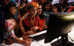 A stockbroker and her family watch a computer screen during a special muhurat trading session in Mumbai, India