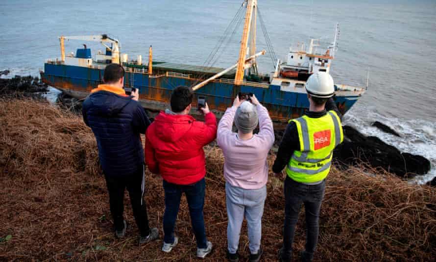 People take photographs of the abandoned cargo ship MV Alta, stuck on rocks near Ballycotton, south-east of Cork