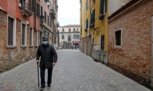 An elderly man walks down a deserted street in Venice