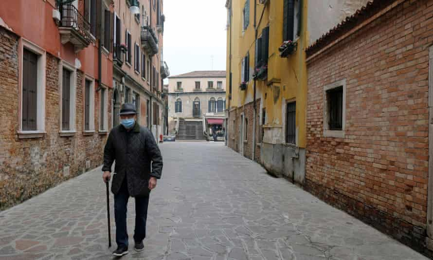 An elderly man walks down a deserted street in Venice