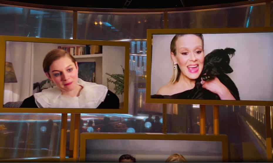 Furry photobomber ... Emma Corrin and Sarah Paulson (with furry friend) speak during the Golden Globe awards ceremony.