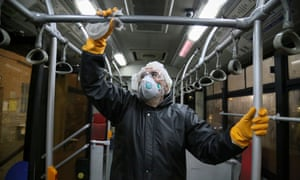 A Tehran municipality worker cleaning a bus