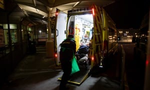 A patient is stretchered out of an ambulance at the emergency department of University Hospital, Coventry, during the coronavirus pandemic