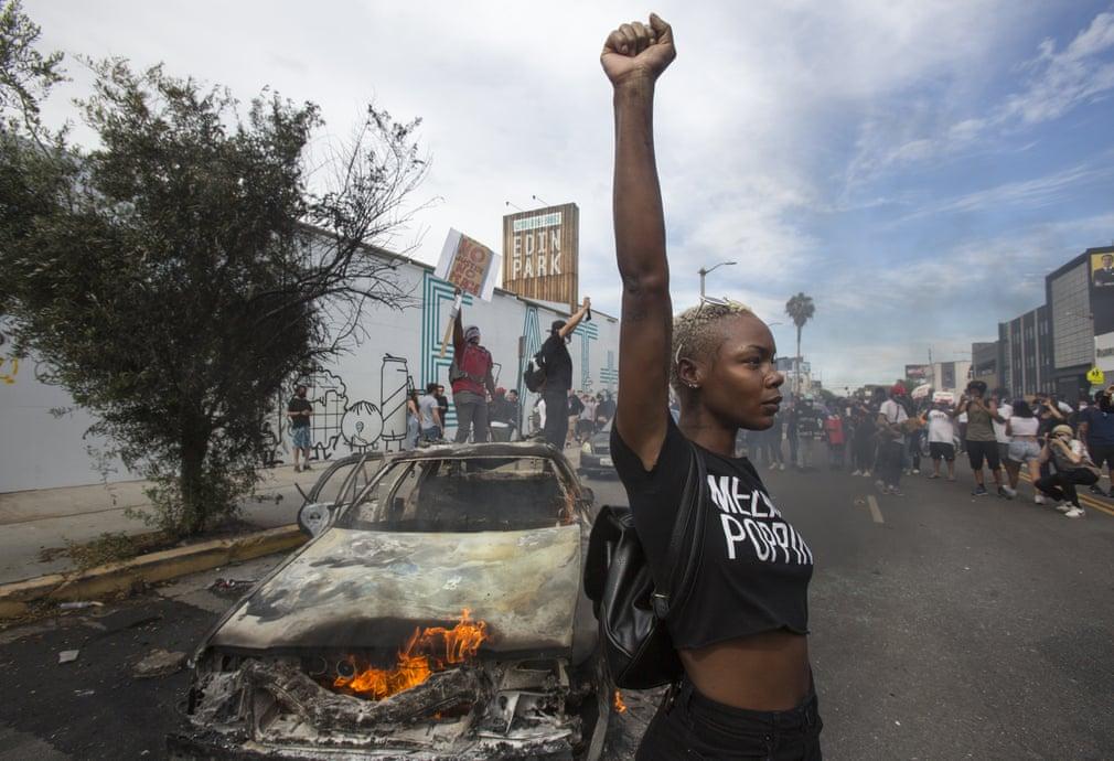 Los Angeles - Una ragazza alza il pugno davanti a un veicolo della polizia in fiamme (Fonte: Guardian; Photograph: Ringo H W Chiu/AP).